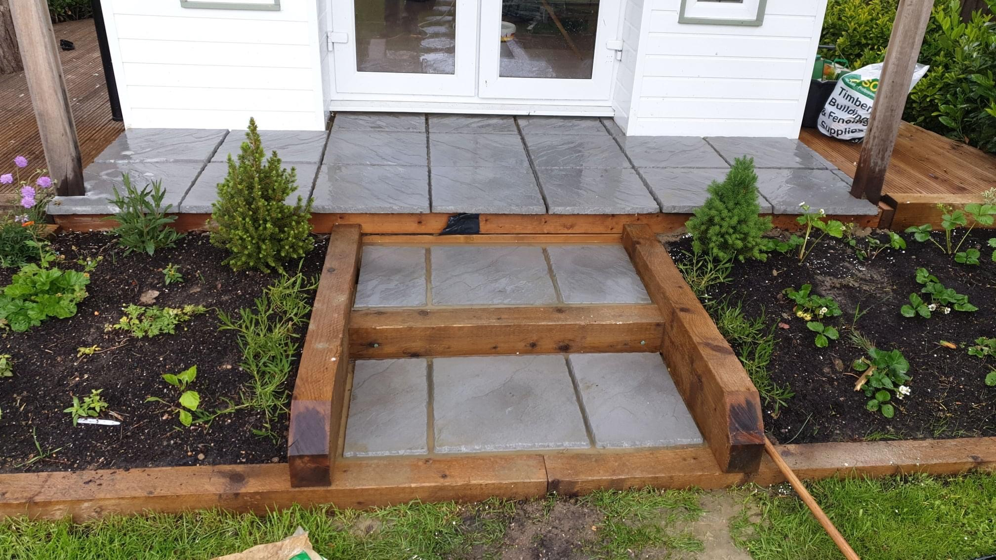 Landscaped patio steps leading to outdoor building in Horsham.